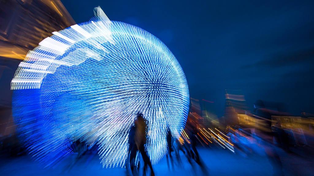 People walk at Manezhnaya Square illuminated to celebrate the upcomin