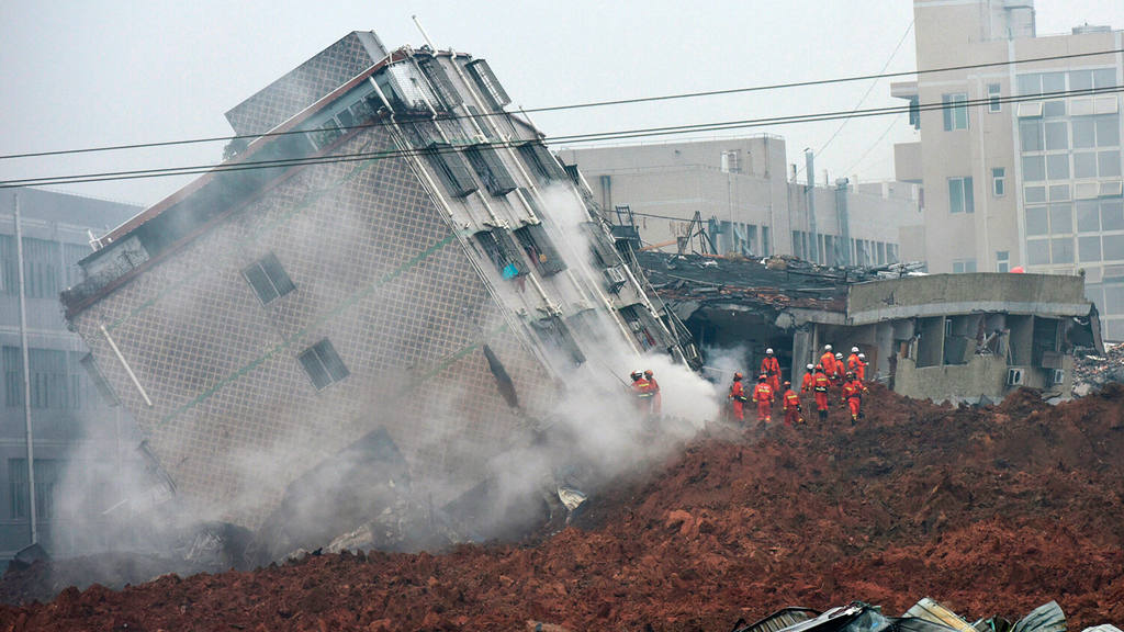 Rescuers search for survivors on a collapsed building following a lan