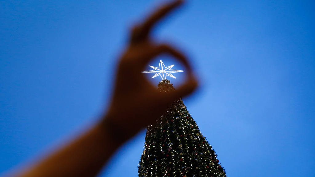 A tourist takes a souvenir photograph in front of a Christmas tree at