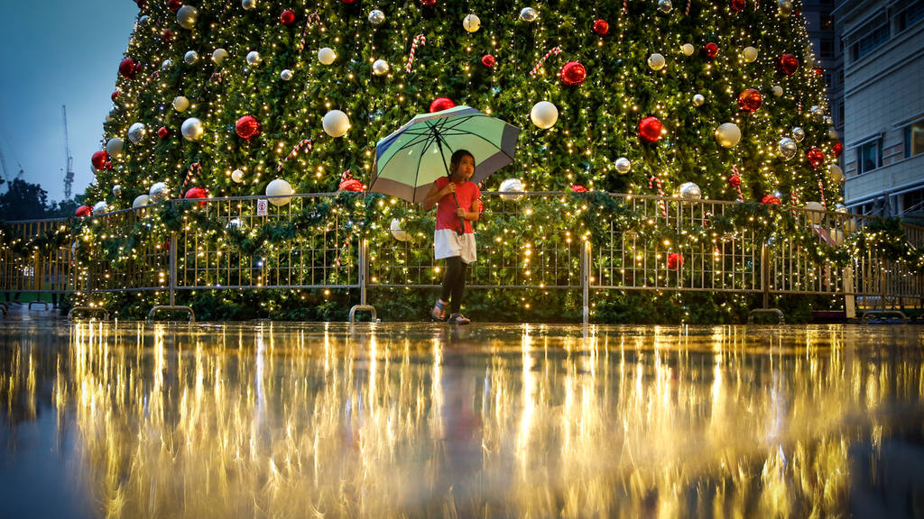 A young Malaysian girl walks in front of a Christmas tree at a mall i