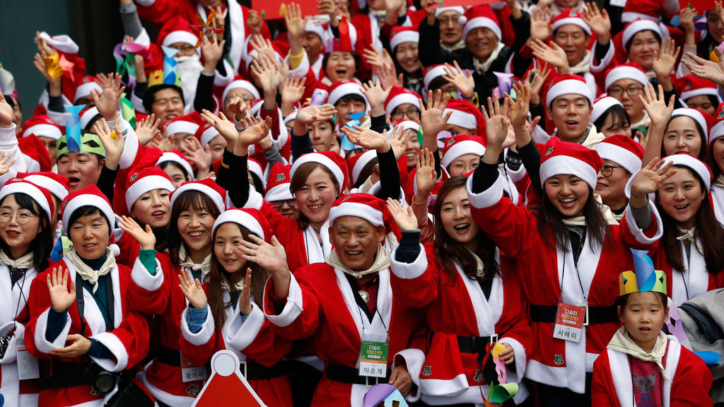 Volunteers, dressed in Santa Claus costumes wave their hands during a