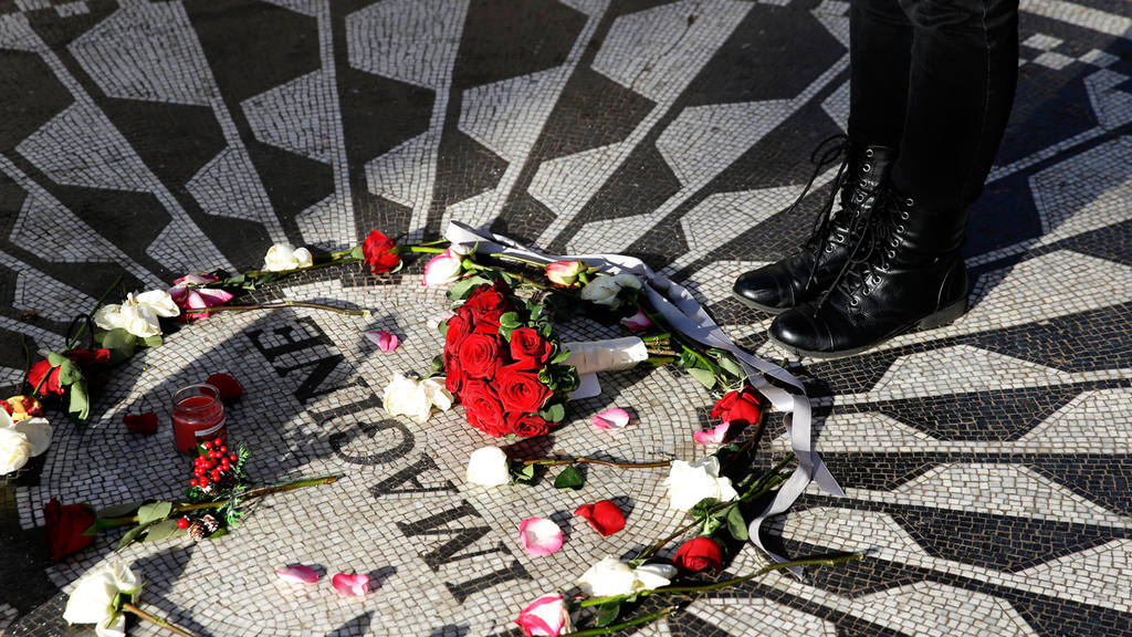 Flowers are arranged on a mosiac tribute to John Lennon at Strawberry