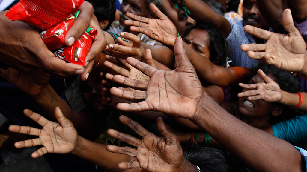 People reach out to collect relief materials being distributed in Che