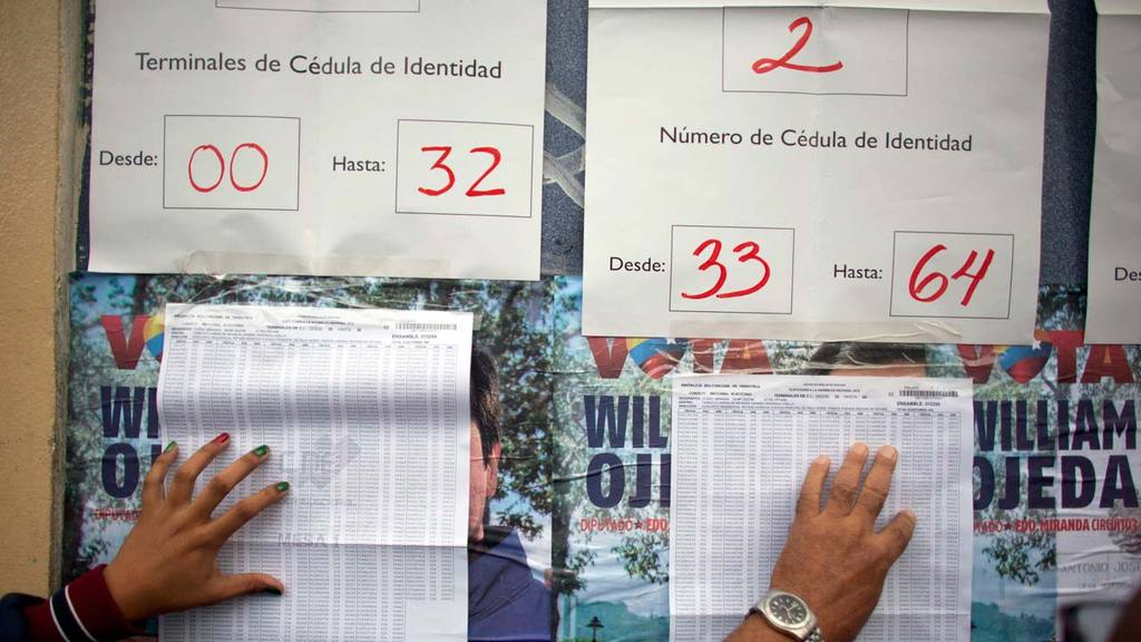 Voters look for their national identification numbers outside a polli