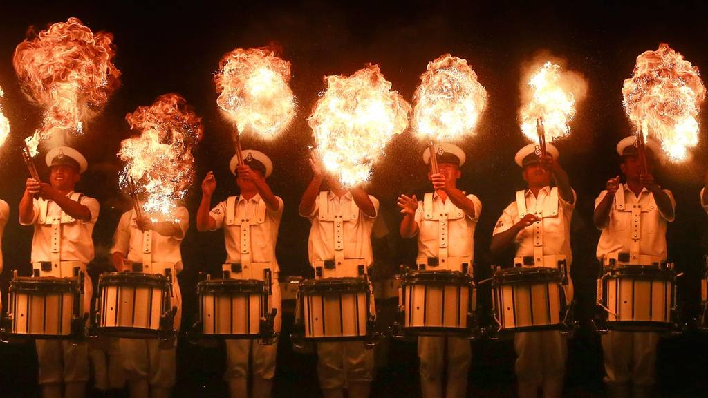 Members of the Indian Navy band perform a fire act during rehearsals