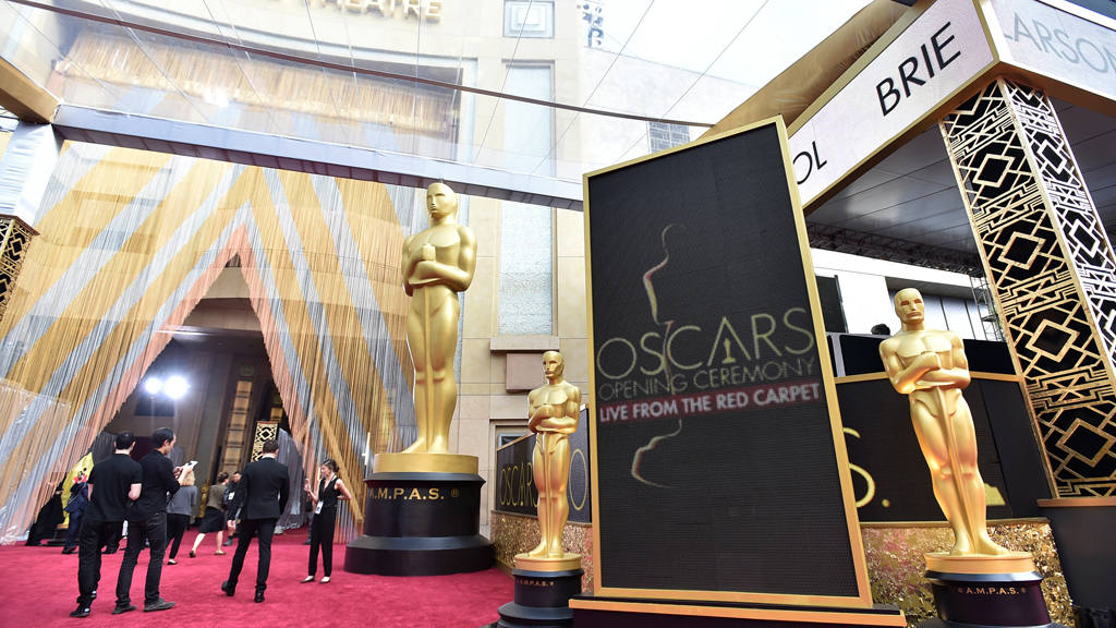 People mingle by Academy Award statuettes on display at Oscars on Sun