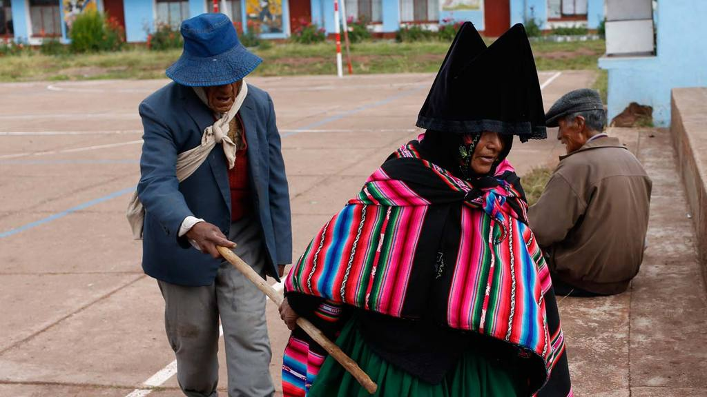 An Aymara woman guides a blind relative to vote at a polling station