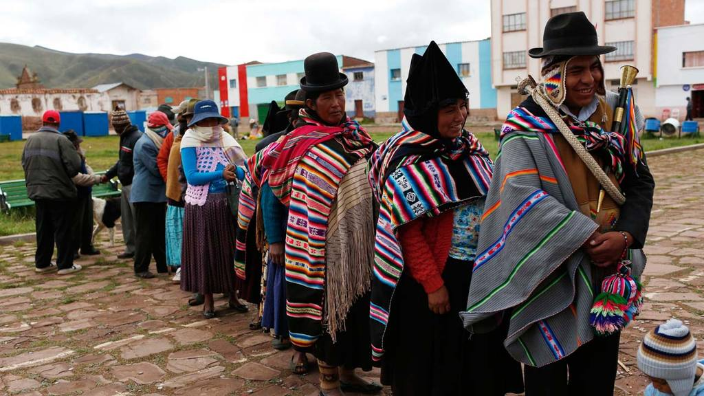 Aymara Indians line up to vote at a voting center during the constitu