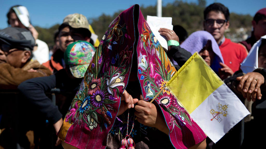 An indigenous woman holding a Vatican flag shades herself with a trad