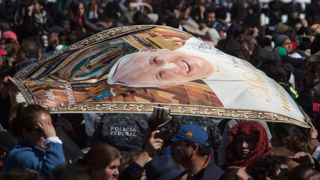 People wave a blanket with an image of Pope Francis at Mexico City's