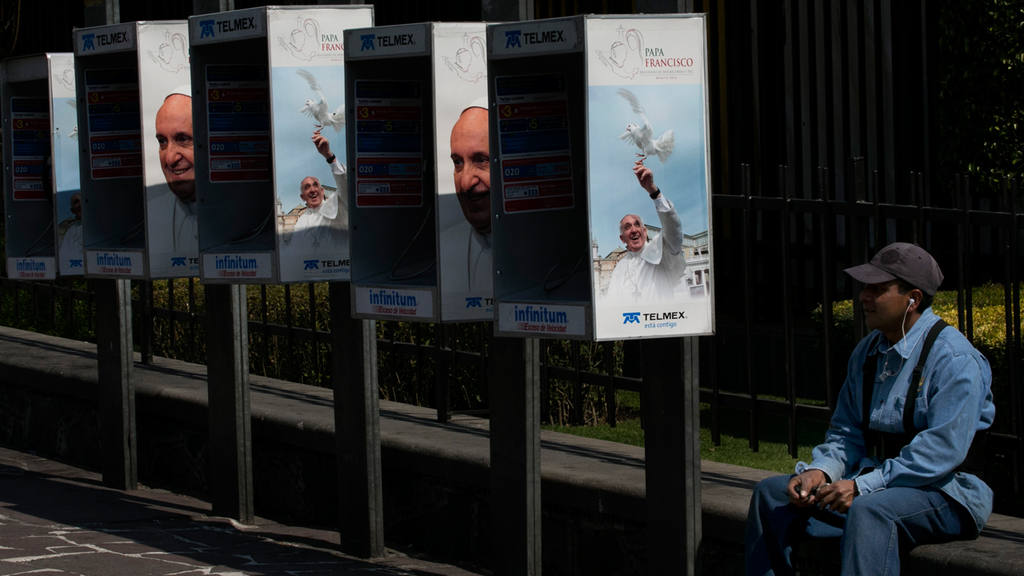 A man sits by public phone booths covered in images of Pope Francis o