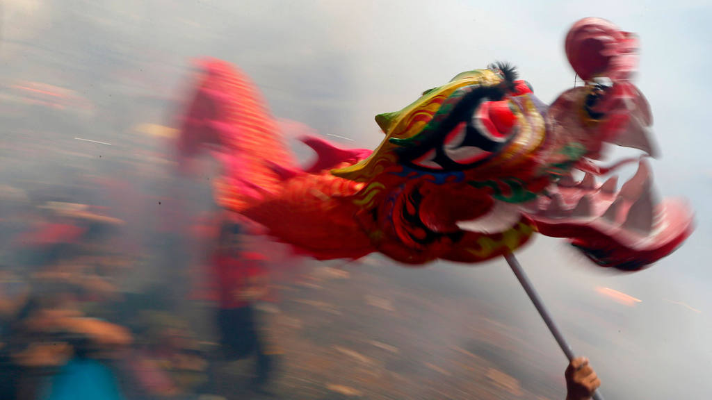 Dragon and lion dancers perform amidst exploding firecrackers in cele