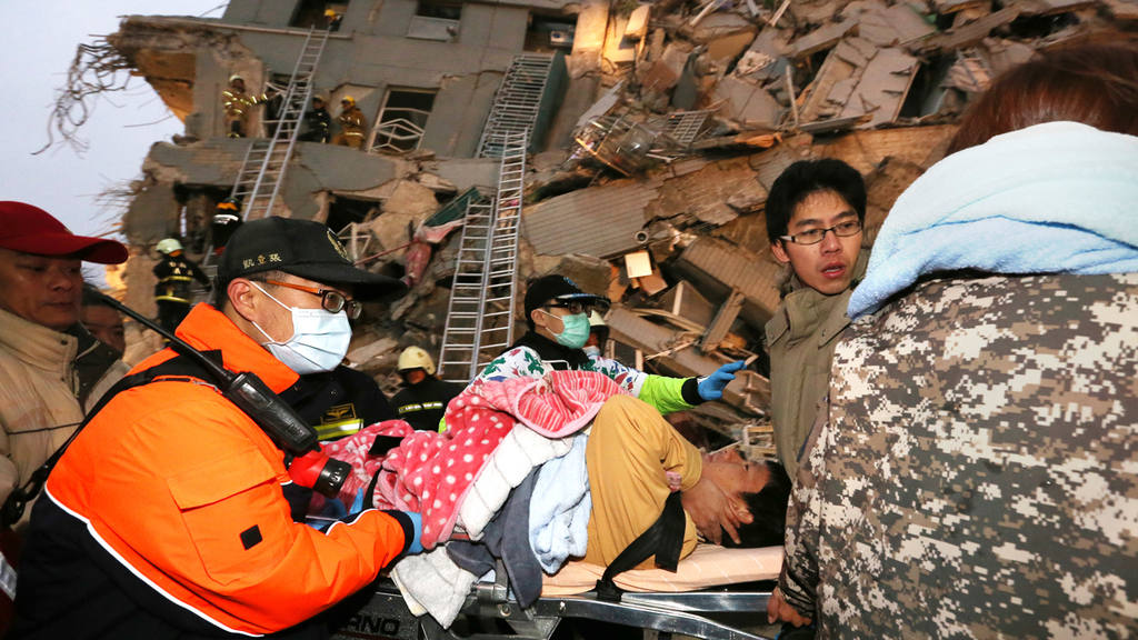 Rescue workers carry a man from the site of a toppled building after