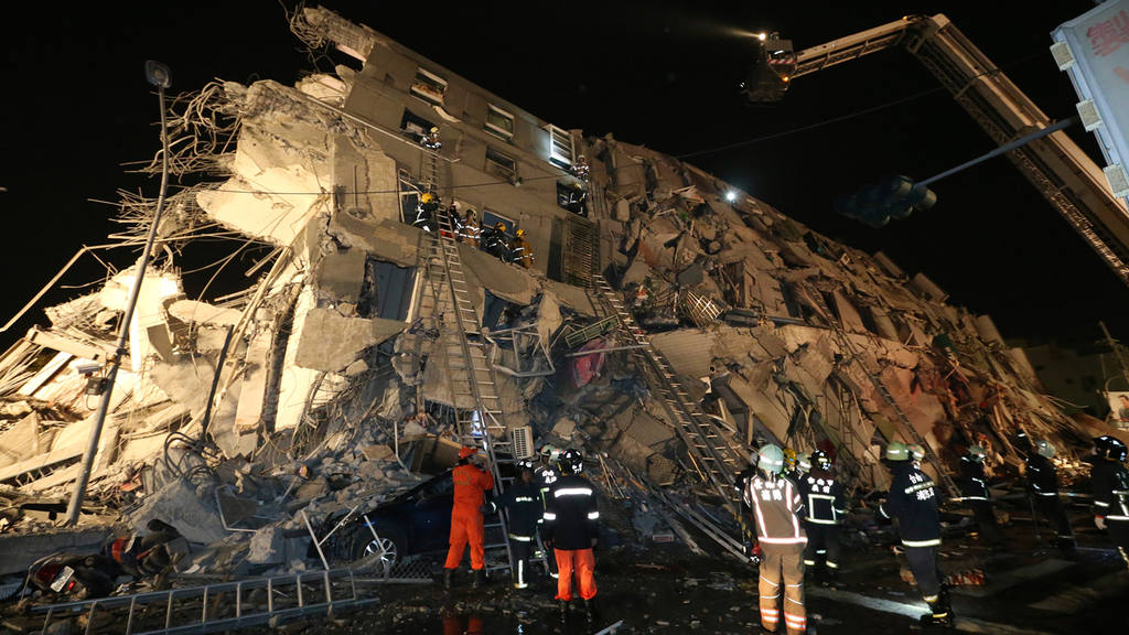 Rescue workers search a toppled building after an earthquake in Taina