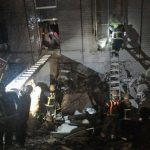 Rescuers are seen entering an office building that collapsed on its s
