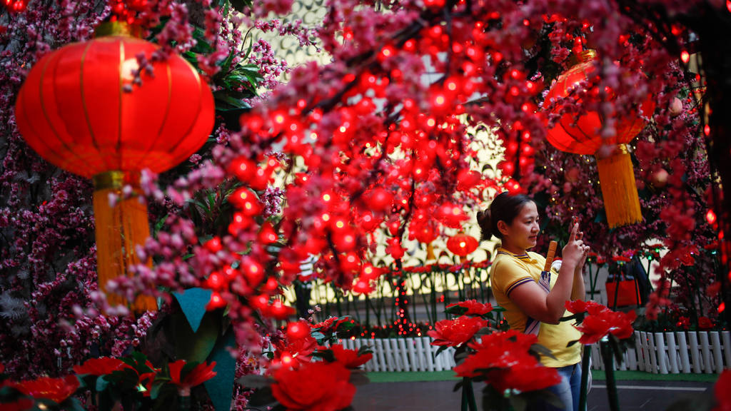 A Malaysian ethnic Chinese woman takes souvenir photographs in front