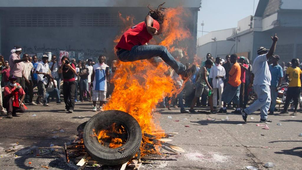 A protester is jumps over a burning barricade during protest against