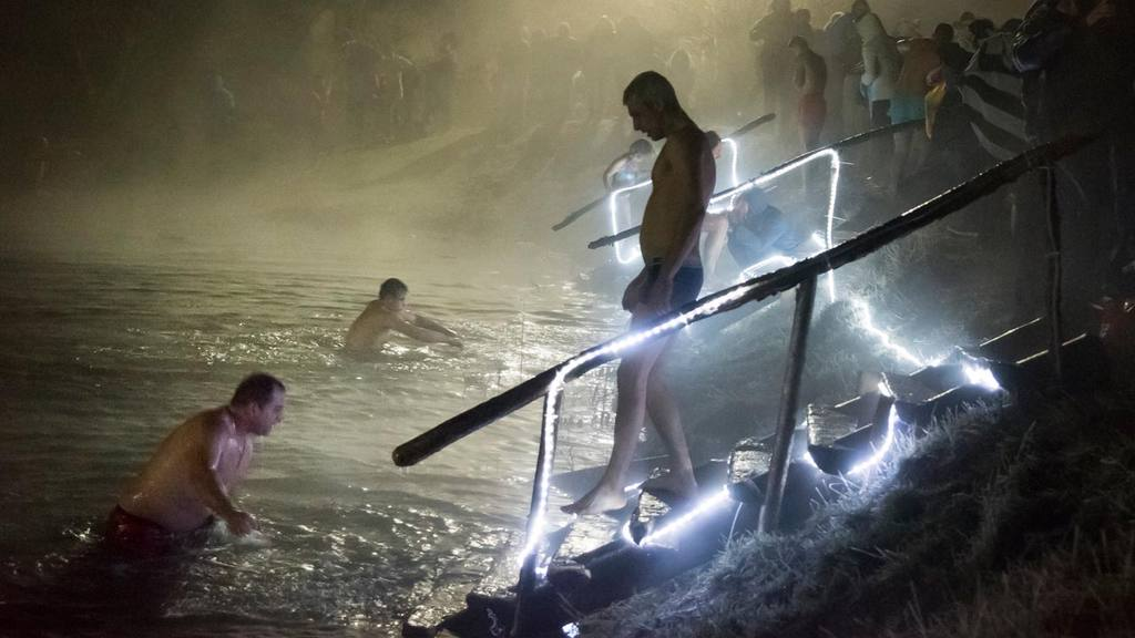 Russian Orthodox believers bathe in ice water in a pond to mark Epiph