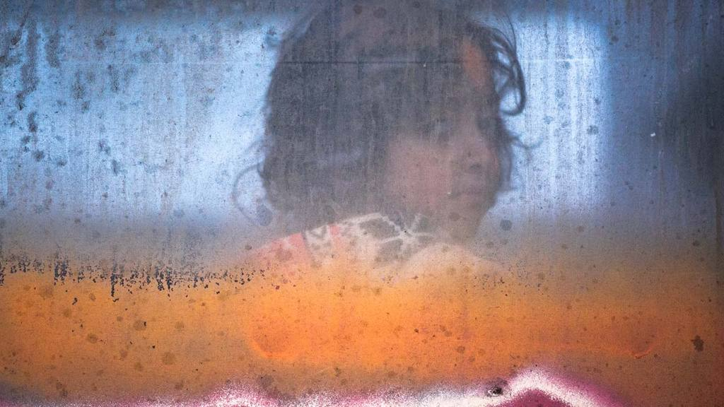 Migrant child looks out of a window of a passenger train in Presevo