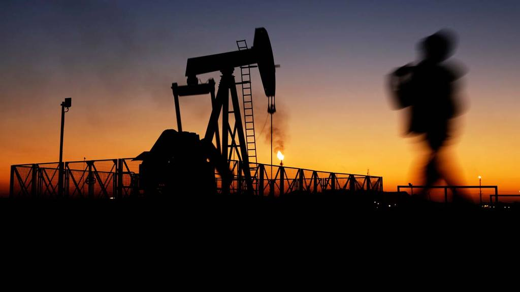 A boy walks by an oil pump at sunset Monday, Jan.