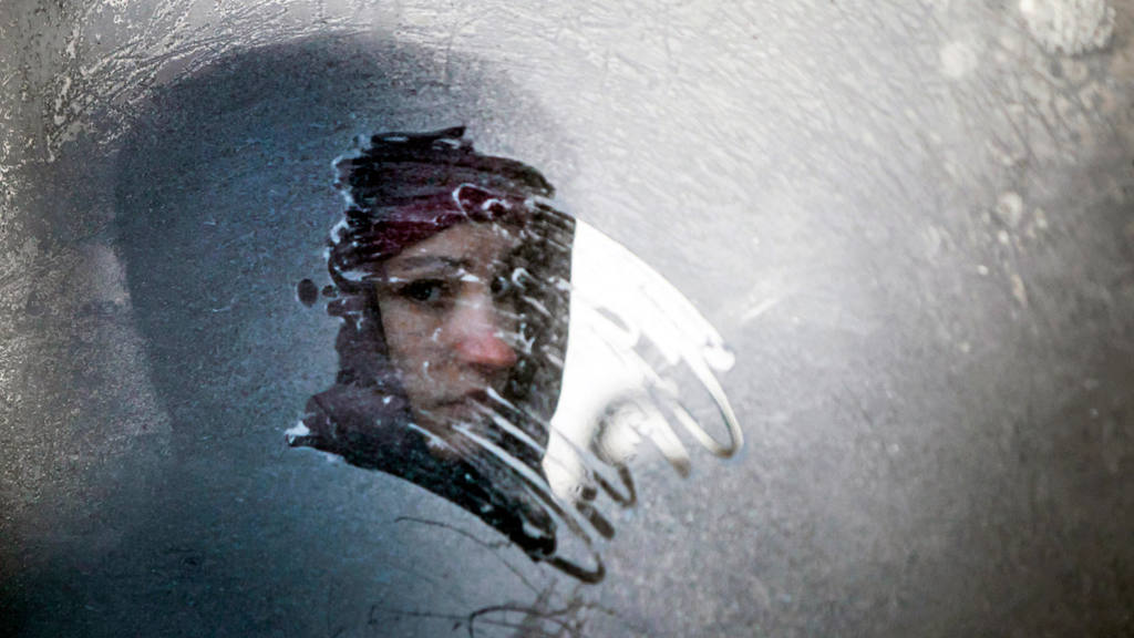 A woman looks through an icy window in a bus in Ukraine's capital in