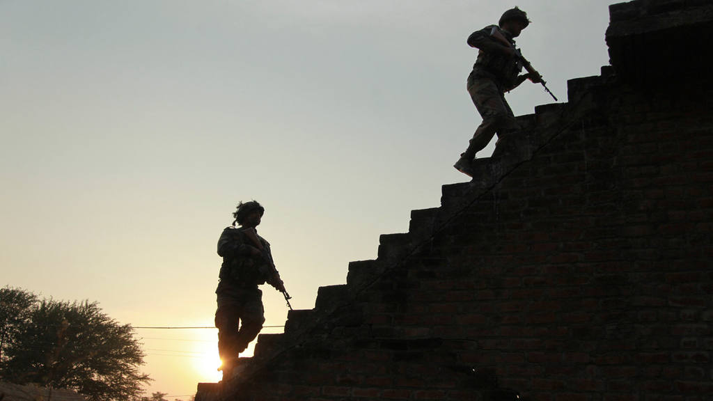Indian army soldiers climb up the stairs of a residential building ou