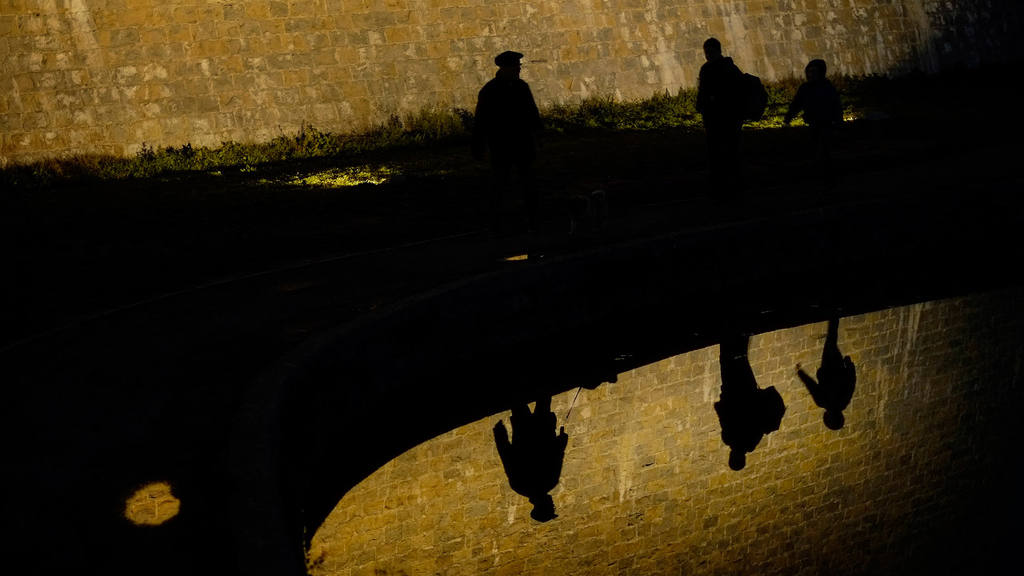 Silhouettes of people are reflected on the water of a pond while they