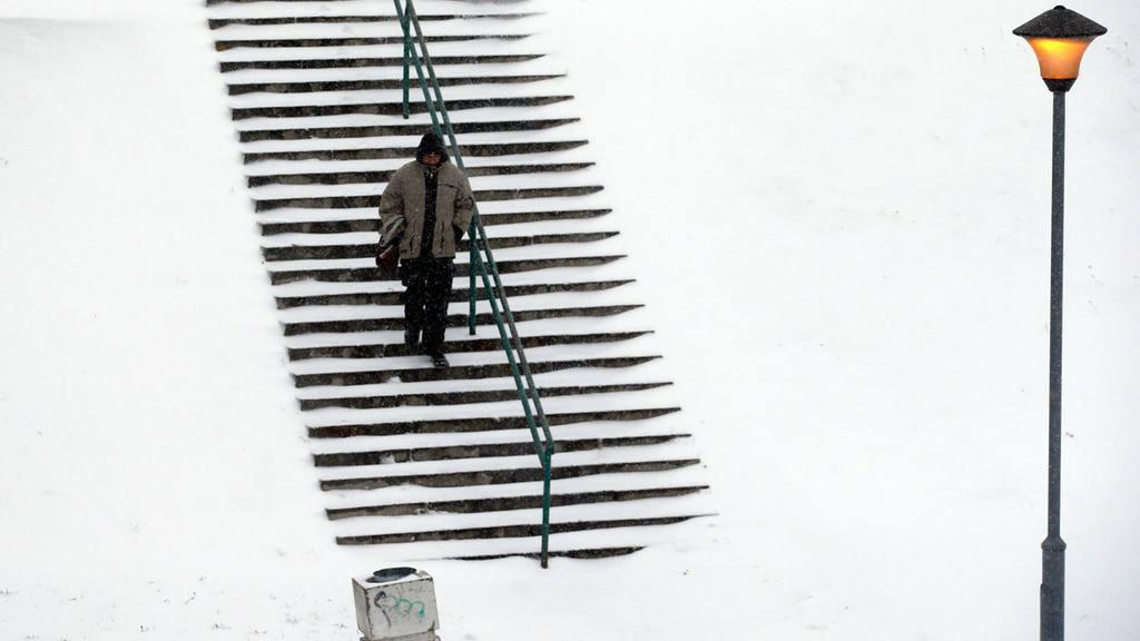 A man walks through the snow covered park in Belgrade