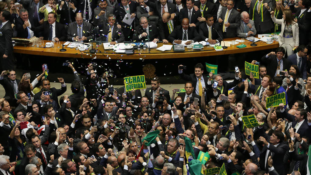 Opposition lawmakers celebrate after the lower house of Congress vote