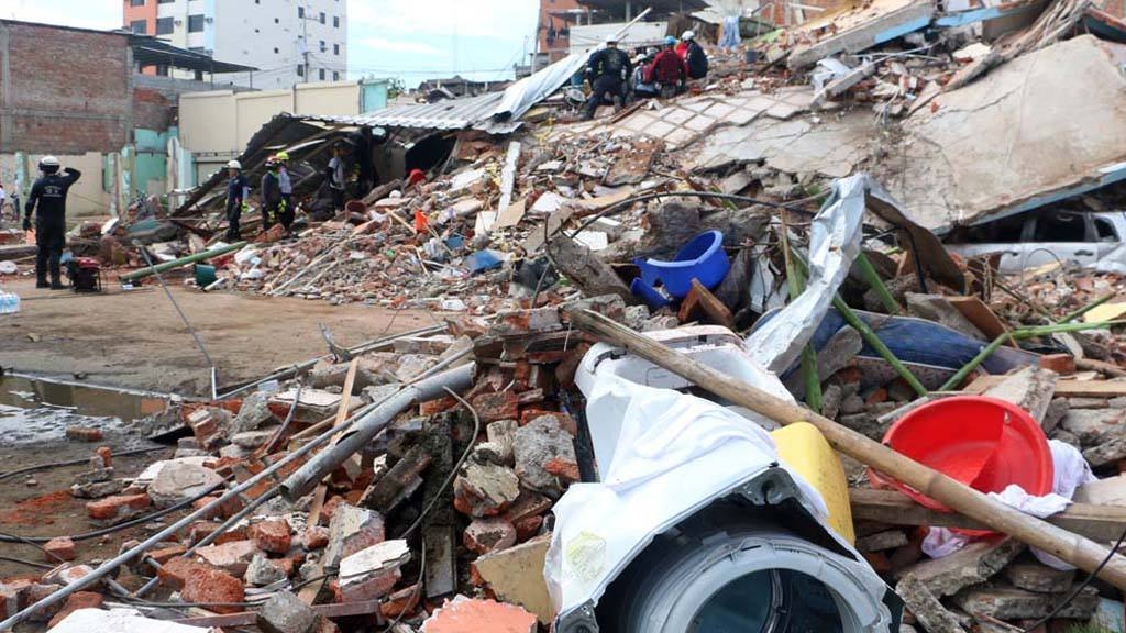 Volunteers and rescue workers search in the rubble of a collapsed bui