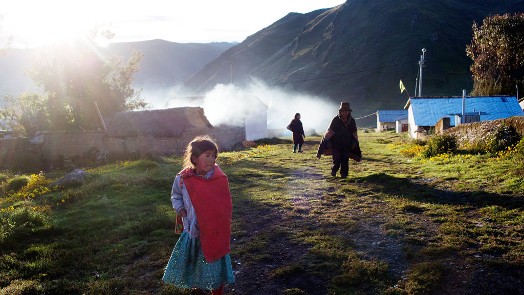 A Quechua indigenous girl watches electoral workers and soldiers as a