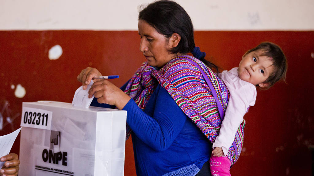 A Quechua indigenous woman carries her daughter while voting during g