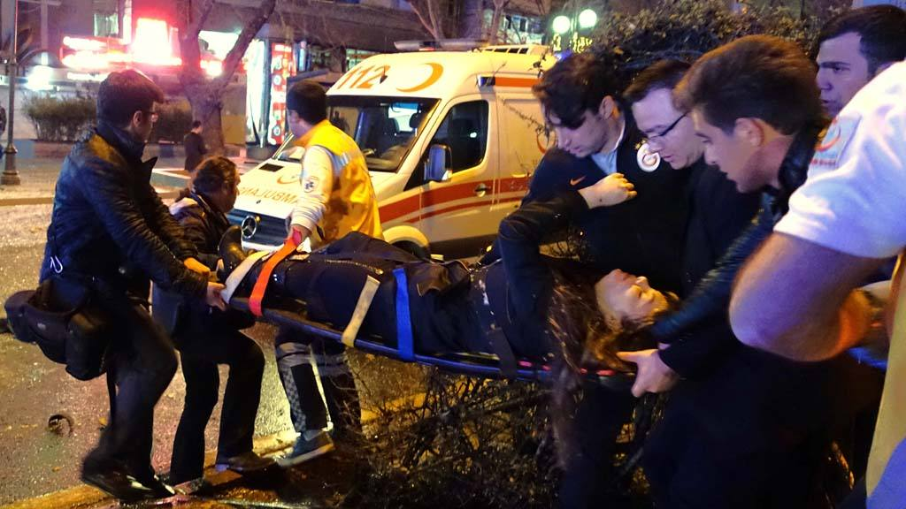 Medics carry an injured at the explosion site in the busy center of T