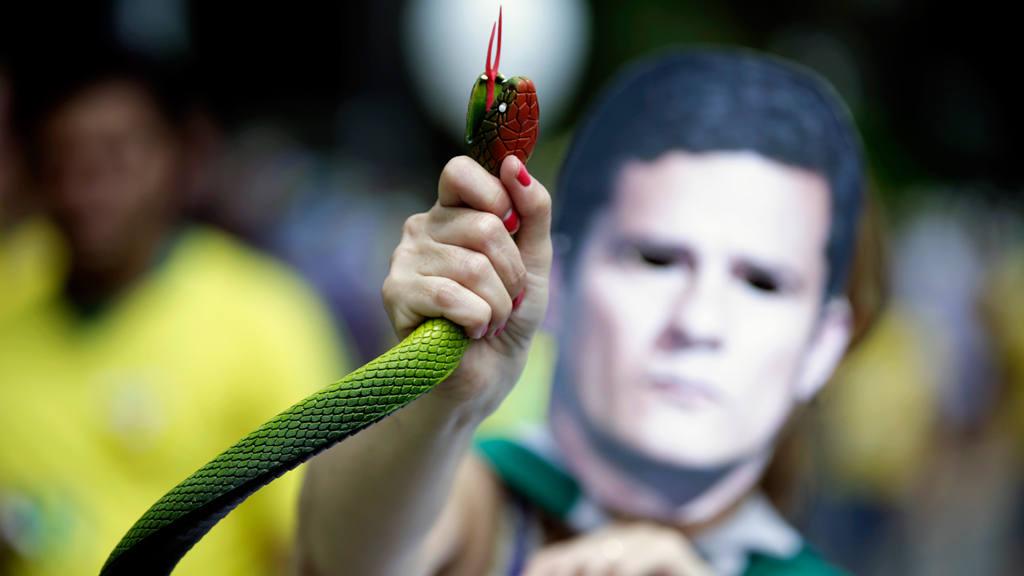 Una persona sostiene una serpiente de juguete mientras unas 100.000 personas protestan.