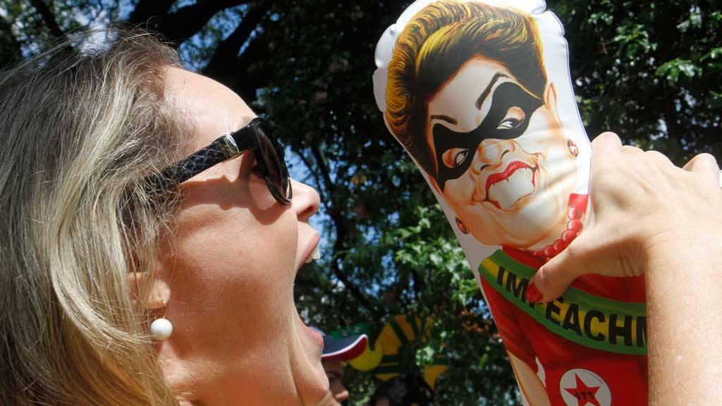 Una mujer sostiene un muñeco con la imagen de la presidenta Dilma Rousseff exigiendo su renuncia.