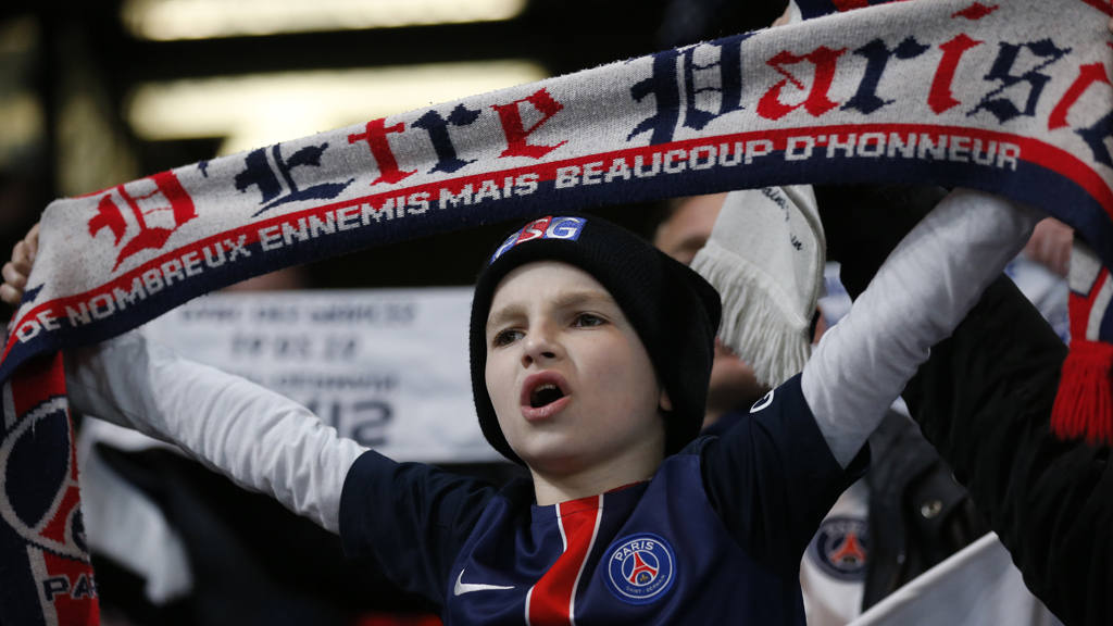 A young boy who supports PSG holds his teams scarf above his head as