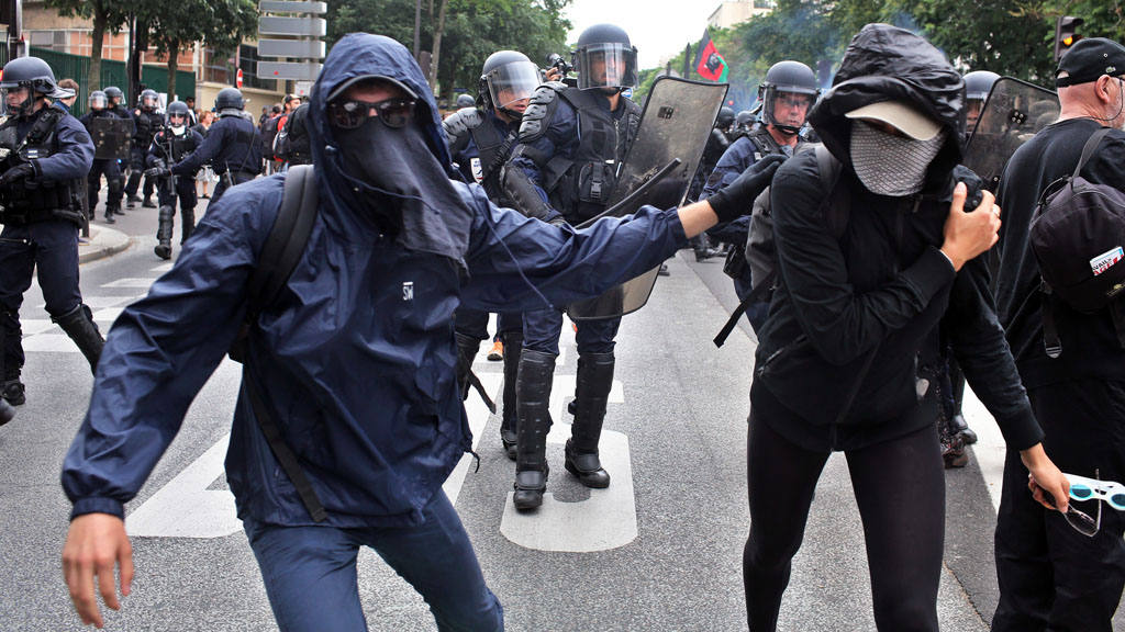 Protestors run away from riot police officers during clashes as part