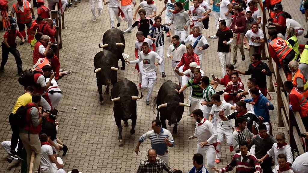 Revelers run beside Victoriano del Rio Cortes's fighting bulls during