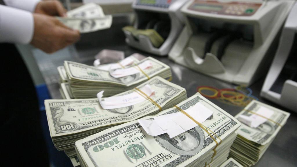 Un cajero cuenta billetes de dólar.