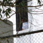 El exalcalde opositor Daniel Ceballos protesta asomado a la ventana de su celda.