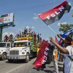 Seguidores del gobernante Frente Sandinista de Liberación Nacional (FSLN) gritan consignas contra una caravana de la oposición .