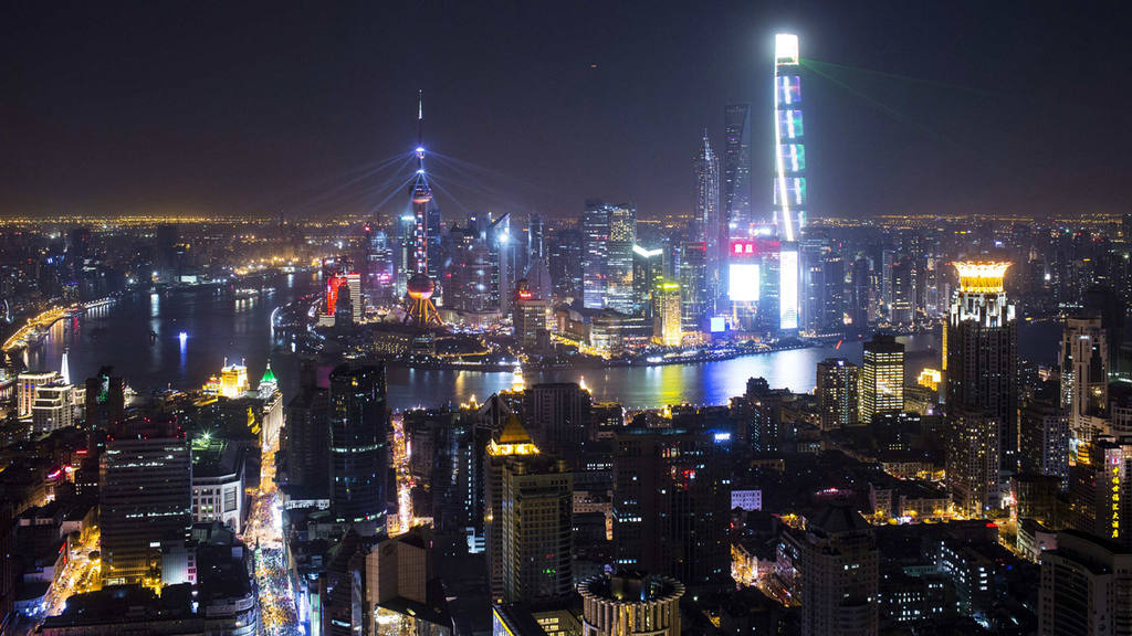 Light and laser illuminate the Lujiazui financial district of Pudong in Shanghai during a light show as part of a New Year countdown celebration on the Bund in Shanghai