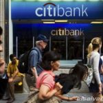 Pedestrians walk past the facade of a Citibank building in New York