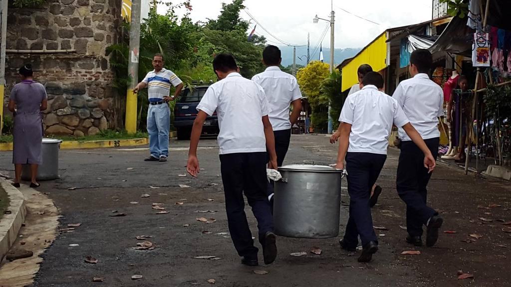 Debido a que la cocina está fuera del centro escolar, los alumnos mayores ayudan a cargar las ollas con alimentos para la hora del refrigerio.