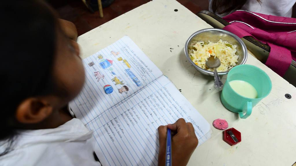 Una niña aprovechaba para adelantar la tarea pendiente mientras recibía el refrigerio escolar.