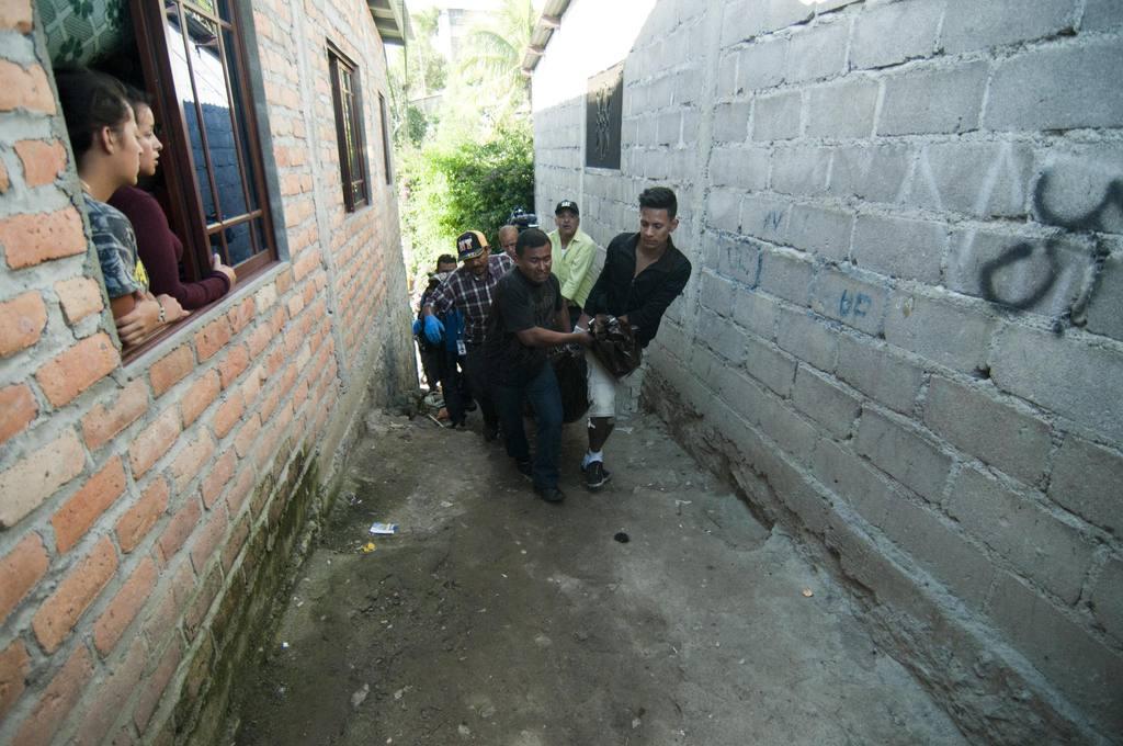 Amigos y familiares cargan el cadáver de una de las siete personas que fueron asesinados el 25 de noviembre.