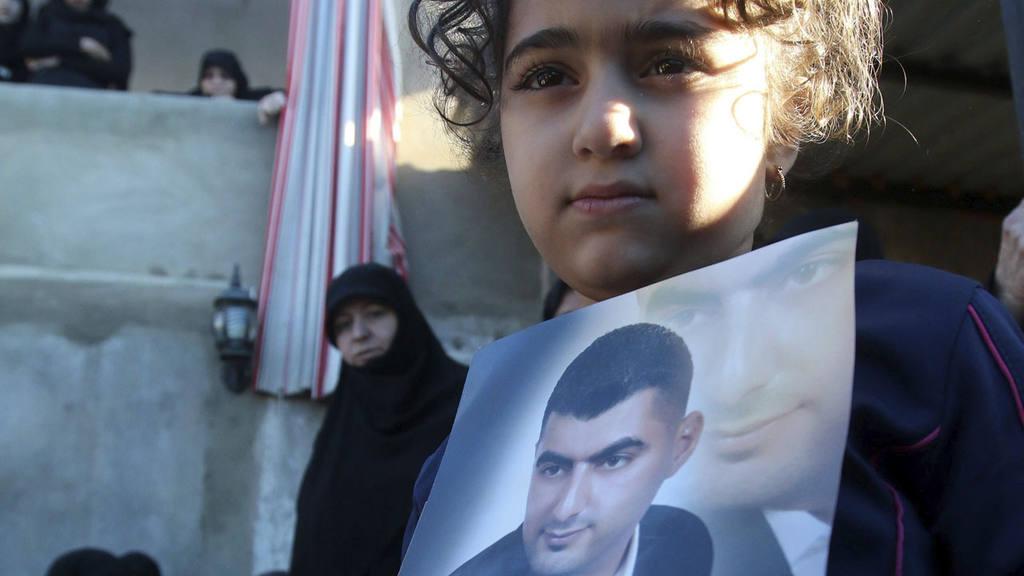 La hija de Adel Tormos, el héroe que se lanzó contra un suicida del Estado Islámico, sujeta una fotografía de su padre durante su funeral en Tallusah, LÌbano.