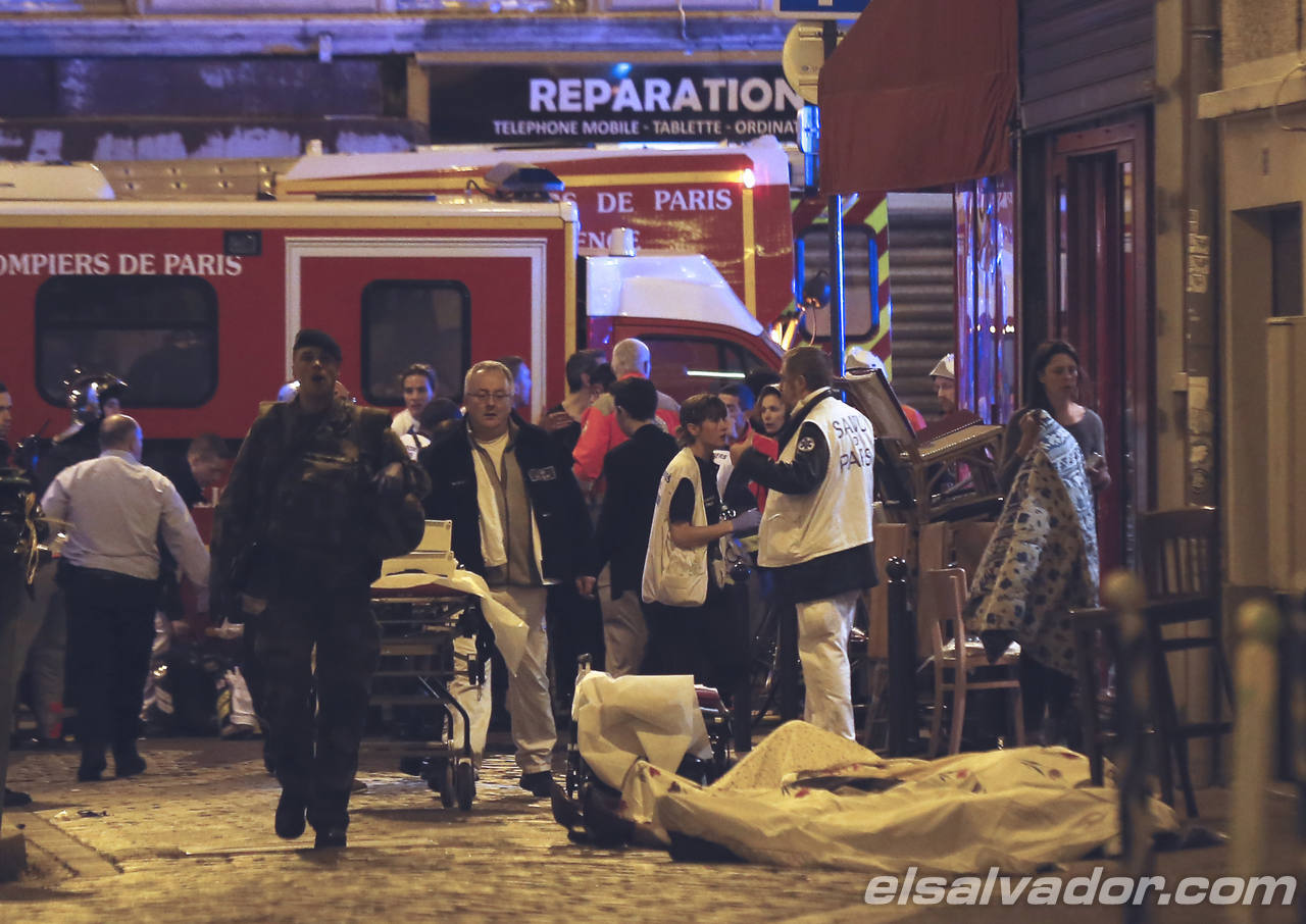 Police officers and rescue workers gather around a victim outside in