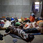 Un grupo de cubanos descansa en afuera del edificio de control de fronteras en Peñas Blancas, en Costa Rica.