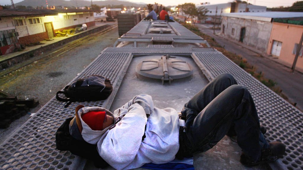 A Central American migrant waits for a freight train to reach and cross the U.S. border, in Arriaga in the state of Chiapas